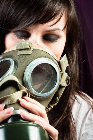 Beautiful girl is holding an old gasmask against dark background photo
