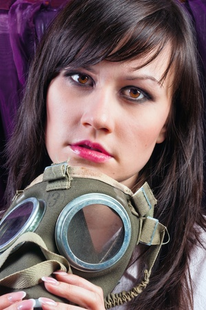 Portrait of a young woman holding her gasmask tight photo