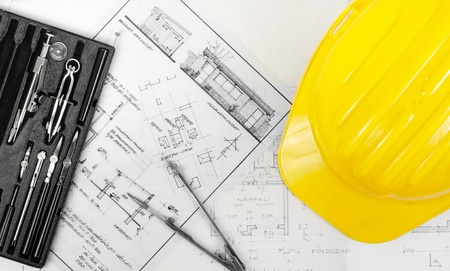 Construction plans with yellow helmet on it photo