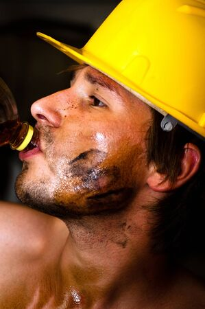 Industrial worker with oil on his face drinking after job photo