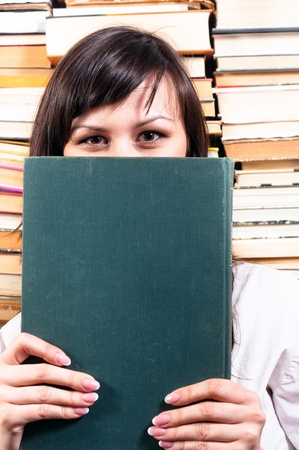 Student girl hiding behind big book Stock Photo - 10536316