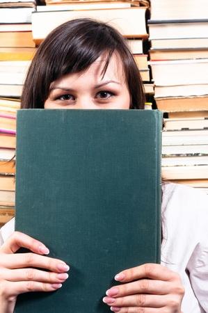 Student girl hiding behind big book Stock Photo - 10536316