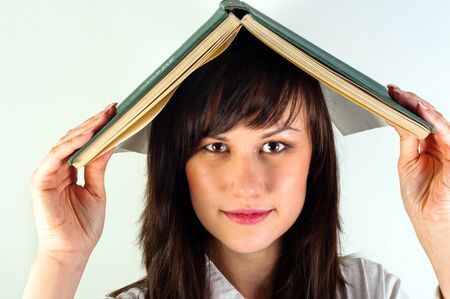 Beautiful young girl hiding under book Stock Photo - 10536356