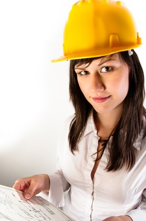 Pretty business woman in yellow helmet holding her plans photo