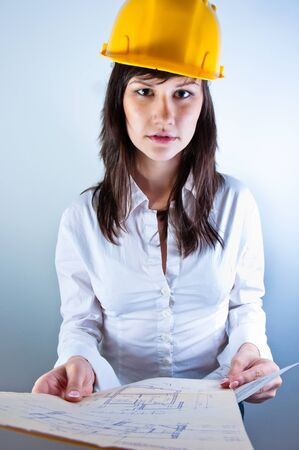 Engineer woman in yellow helmet with plans Stock Photo - 10536346