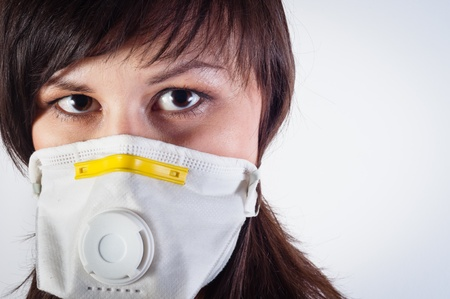 disease prevention: girl wearing protective mask against white background
