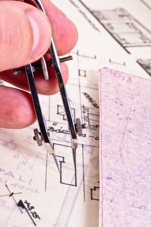 Fingers of an architect drawing a new home photo