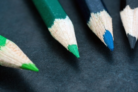 Colorful pencils on dark background lined up photo