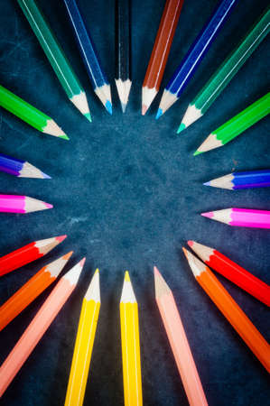 Colorful pencils on dark background in a circle photo