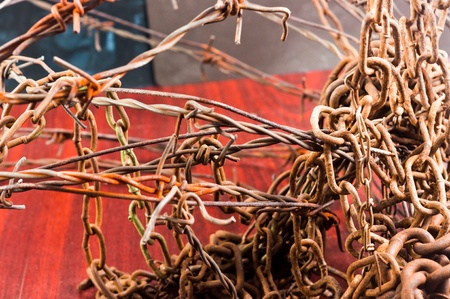 rusting: Barbed wire and chain of sorrow linked in each other Stock Photo