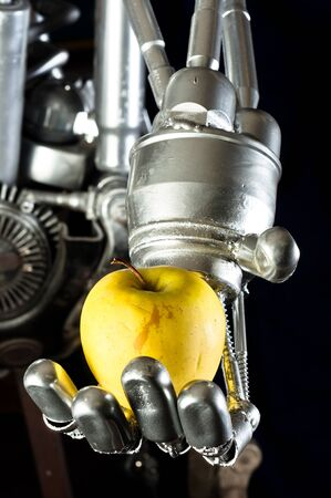 A robot hand with green apple photo