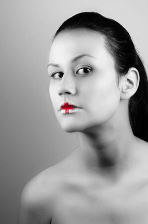 Black and white ohoto of a girl with medical lipstick photo