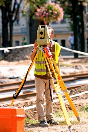 Worker inspecting site  with his tripod and industrial device Stock Photo - 12134670