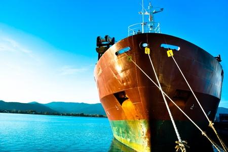 ports: Grande barca di trasporto presso la baia contro il cielo blu