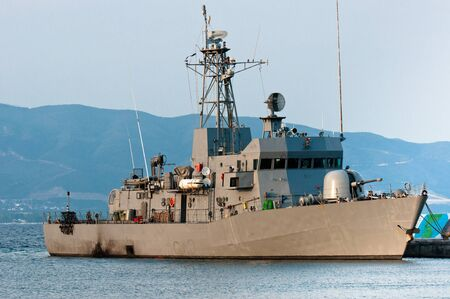destroyer: Big battle ship in the dock against blue sky and mountains Editorial