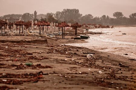 A dirty polluted beach  in the rain Editorial