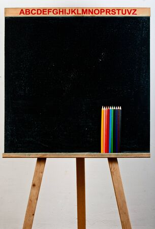 Black chalkboard with pencils against white background photo