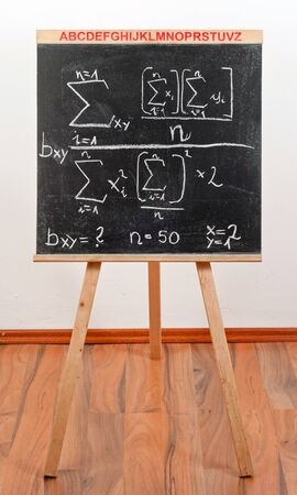 Black chalkboard with formula against white background photo