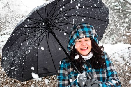 Young woman with umbrella in a blizzard photo