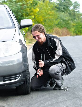Handsome young man repairing flat tire Stock Photo - 12723280