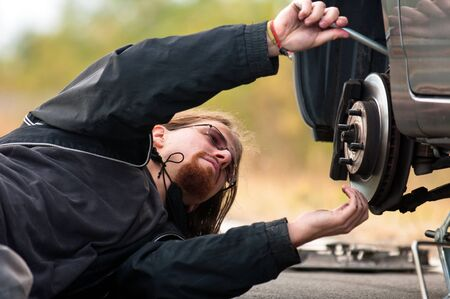 Handsome young man repairing flat tire Stock Photo - 12723276
