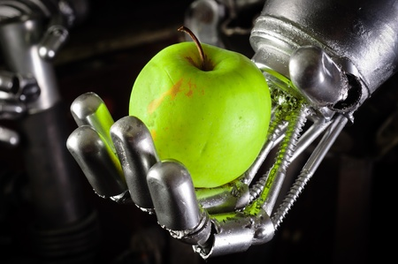A robot hand holding a fresh apple closeup