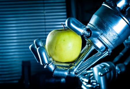 Robot hand holding fresh apple