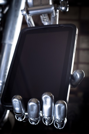 Robot hand holding tablet pc against dark background Stock Photo - 12734835