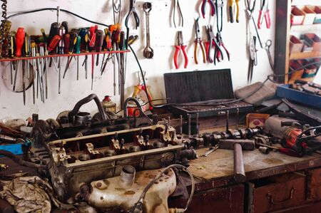dirty room: Many tools in a workshop on a wooden table