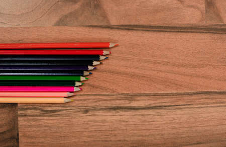 Colorful pencils background on wooden floor photo