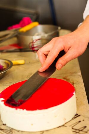 Hand of a confectioner making cake