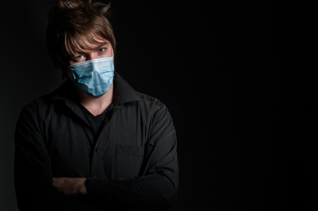 Young man with protective mask on dark background Stock Photo - 13610556