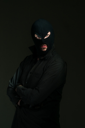 bandit: Thief with blue eyes against dark background Stock Photo