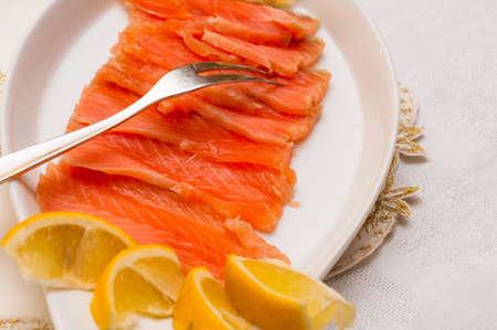 Raw salmon on plate with lemon photo