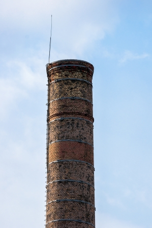 Big industrial chimney against blue sky photo