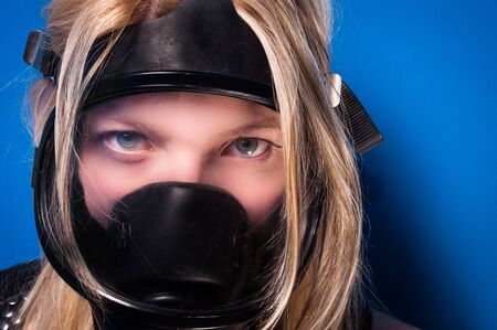 Girl in gasmask against blue wall photo