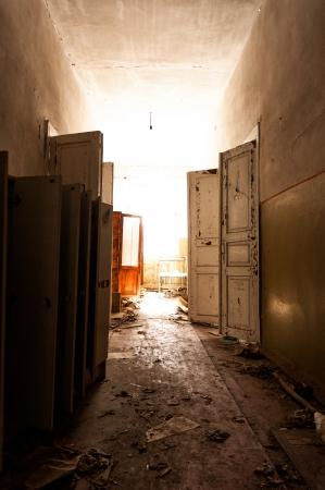 ventana rota: Puerta con la luz brillante en un edificio abandonado