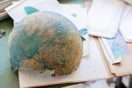 Abandoned and broken globe in a school table photo