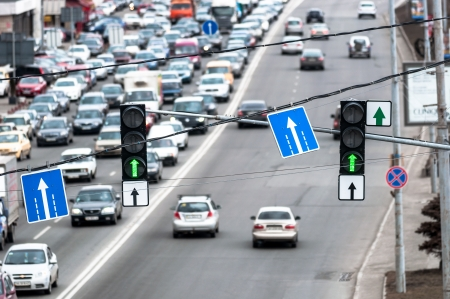 Green traffic lamps and blue sign with blurred cars Stock Photo - 13602195