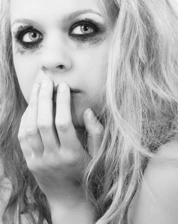 A sad blond girl with terrified expression closeup photo