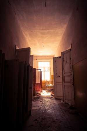 horror background: Doorway with bright light in an abandoned building Stock Photo