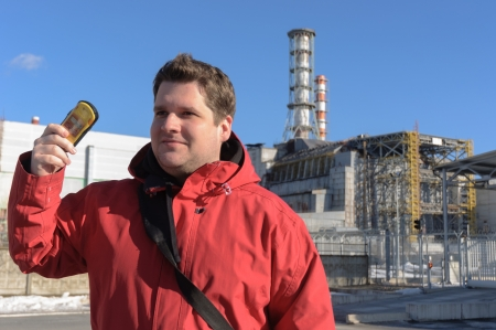 Handsome young explorer and the power plant at Chernobyl Stock Photo - 14301631