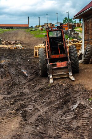 Red tractor in the mud outdoors photo
