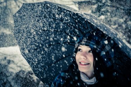 blizzard: Junge Frau mit Regenschirm in einem Schneesturm