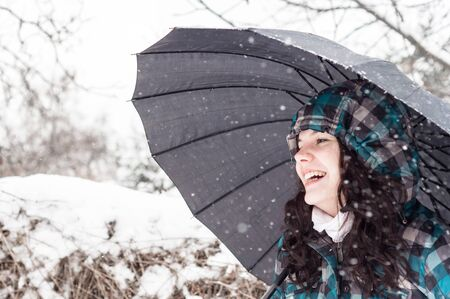 Girl with umbrella in the snow closeup photo
