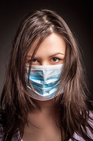 Young woman in a protective mask against dark background photo