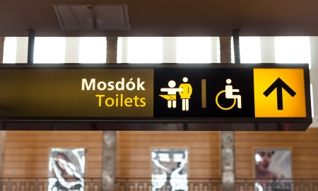 Toilet sign on wall glowing in yellow photo