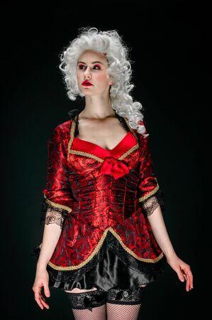 Girl in baroque dress against black background photo