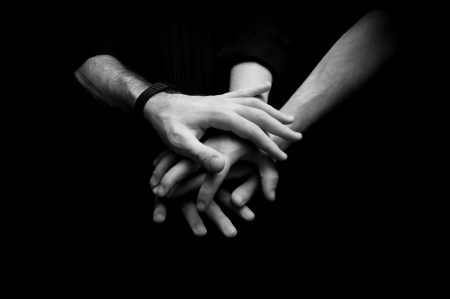 strength in unity: Group of young adults making a pile of hands against dark background