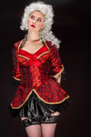 Young woman in baroque costume against dark background photo